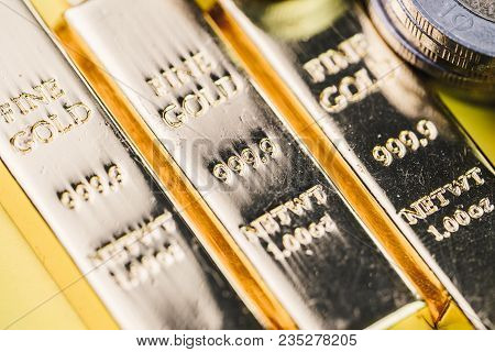 Pure 999.9 shiny fine gold bullions ingot bars with money coins, closed up macro shot as financial asset, investment and wealth concept. poster