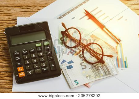 Tax Calculation Or Budget Planning Concept, Eyeglasses, Pen On Pile Of Euro Banknotes On Graph And C