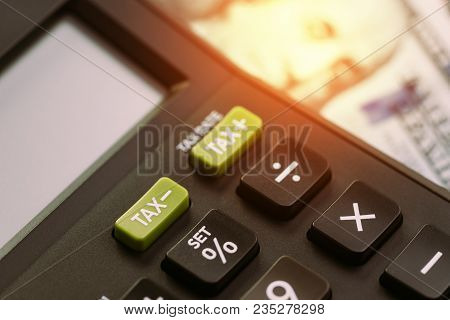Tax Cuts Or Reduce Concept, Selective Focus On Tax Minus Buttons On Calculator With Background Of Bl