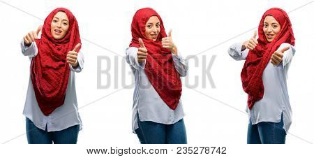 Arab woman wearing hijab stand happy and positive with thumbs up approving with a big smile expressing okay gesture isolated over white background