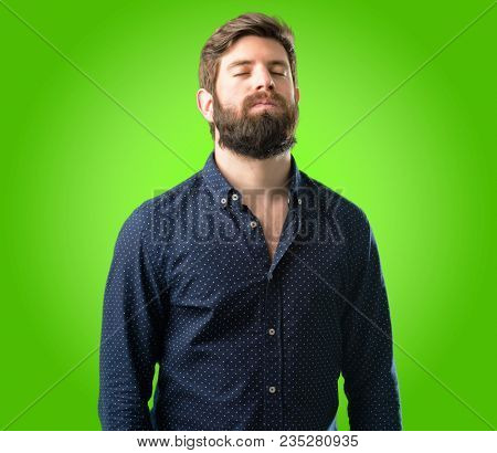 Young hipster man with big beard with sleepy expression, being overworked and tired over green background