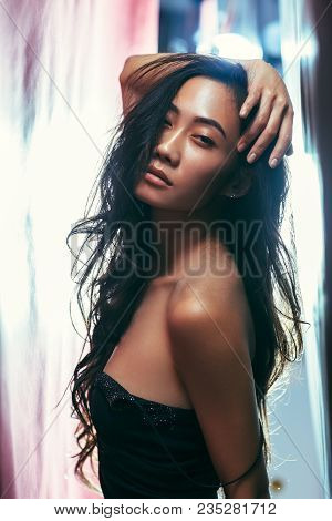 Asian Girl In Dress With Bare Shoulder. Model With Curly Long Hair, Hand On Head Posing On Light Bac