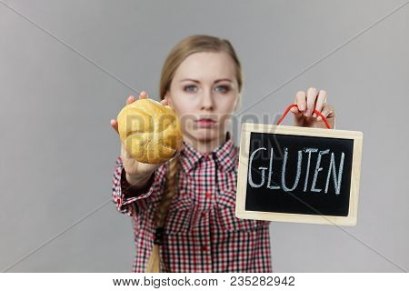 Young Woman With Braided Hair Holding Small Black Board With Gluten Sign And Bun Bread Roll. Bakery