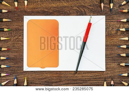 Background Or Background From Pencils On Wooden Table. In The Center Is A White Sheet With A Yellow