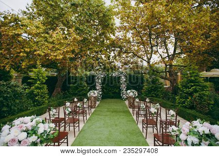 Beautiful Decoration Of A Wedding Ceremony In A Green Autumn Garden. Brown Wooden Chairs For Guests