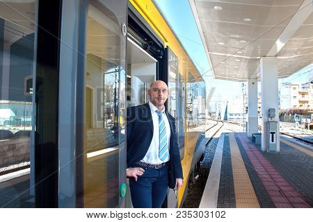 Portrait of the train conductor middle aged waiting passengers to board. Modern train at the European station in summer. poster