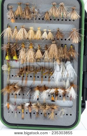 Dry Flies In A Fly Box Or Case Ready For Fly Fishing Shot On A White Isolated Background In Studio.