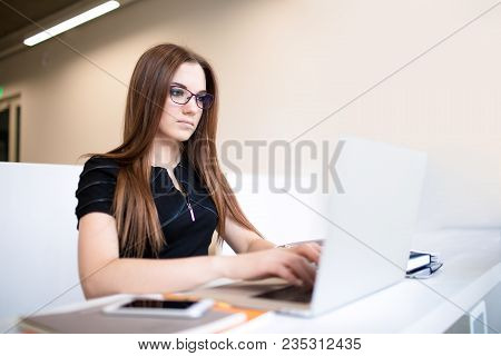 Woman Marketing Specialist Working In Internet Via Laptop Computer, Sitting In Modern Office Space.