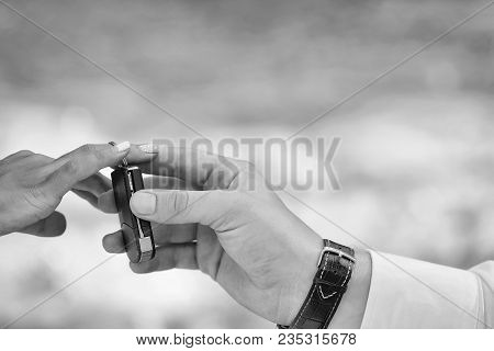 Hands Of Groom Puts Keyless Entry System On Chain On Bride Finger During Wedding Ceremony On Natural