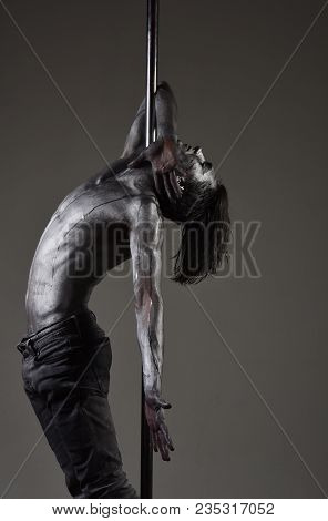 Athlete, Flexible Sportsman Performing Pole Dancing Moves. Artistic Guy Hanging On Metallis Pole. Pe