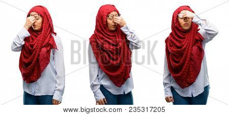 Arab woman wearing hijab with sleepy expression, being overworked and tired, rubbes nose because of weariness isolated over white background