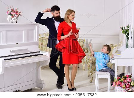 Kid Growthing In Welfare. Mother And Father Stands Near Piano, Watching While Their Son On Busy Face