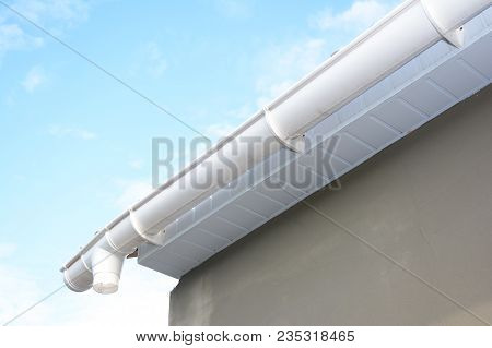 Roof Gutter Repair. Rain Gutter Installation With Drain Downspout Pipe. Guttering With Soffits And F