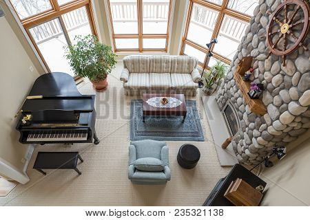 Upscale Living Room Seen From Above Including Piano, Floor To Ceiling Fireplace, And Modern Decor.