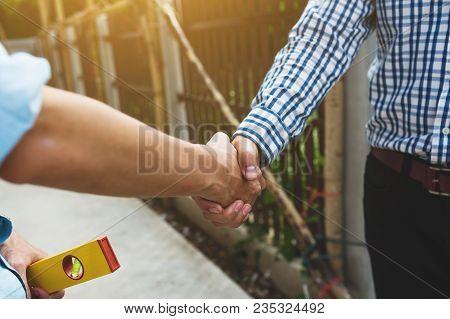 Shaking Hands Of Foreman Engineer Teamwork Deal House Builder, Working Together Concept.
