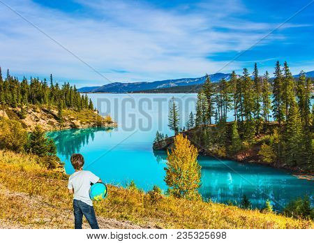 Nine-year-old boy in jeans with a globe in his hands admires the lake. Exquisite Abraham Lake with turquoise water. Indian Summer in the Rockies of Canada. Concept of ecological and active tourism