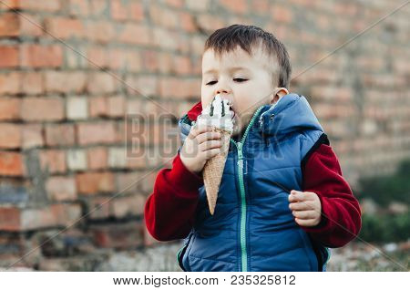 Outdoor Portrait Of A Young Boy Three Years Eating Ice Cream Very Appetizing