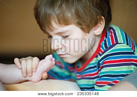Little Kid Boy Kissing And Playing With Foot Of Newborn Baby. Brother Cuddling With New Born Child,