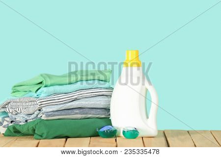 Stack of clothes and laundry detergent on wooden table