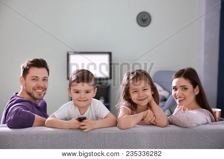 Family watching TV on sofa at home