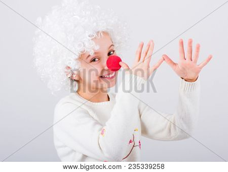 Pretty teen girl in white clown wig and red nose gesturing with hands