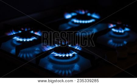 Kitchen gas stove with burning blue gas. Four burning gas hobs in the dark