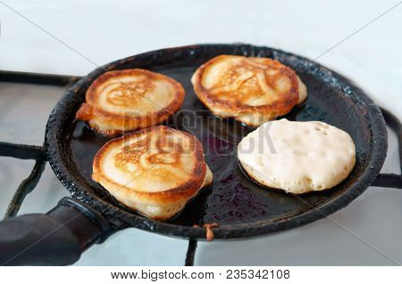 Four Pancakes Are Cooked In Oil On A Frying Pan, Pancakes Are Fried In A Frying Pan