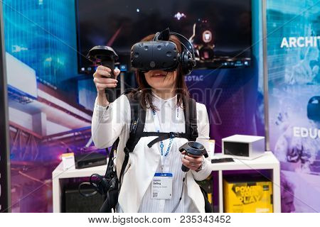 Hannover, Germany - March, 2017: Girl Playing Video Game In Virtual Reality Headset And Handheld Con