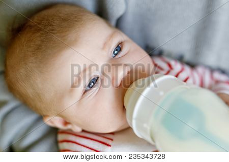 Father Feeding Newborn Baby Daughter With Milk In Nursing Bottle. Formula Drink For Babies. New Born