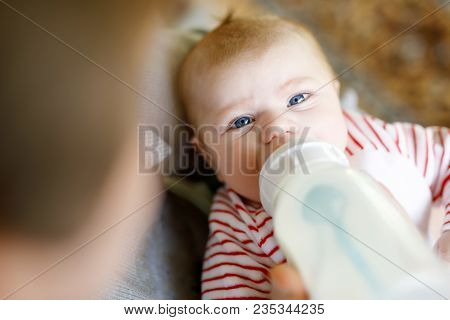 Mother Feeding Newborn Baby Daughter With Milk In Nursing Bottle. Formula Drink For Babies. New Born