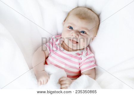 Cute Adorable Newborn Baby In White Bed On A Blanket. New Born Child, Little Adorable Girl Looking S