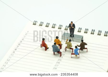 Miniature People Sitting On Red Staples Placed On A Book Rankings (list). Meeting Or Discussion Usin