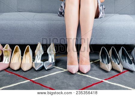 Sexy Woman's Legs In Silver And Pink Glitter High Heel Shoes On Gray Carpet.