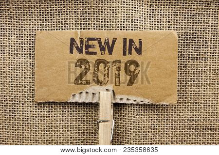 Writing note showing  New In 2019. Business photo showcasing Fresh Era Latest Year Period Season Annual Coming Modern written Cardboard Piece Holding By Clip the jute background. poster