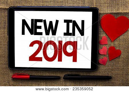 Handwriting text writing New In 2019. Concept meaning Fresh Era Latest Year Period Season Annual Coming Modern written Tablet the jute background Hearts and Pens next to it. poster