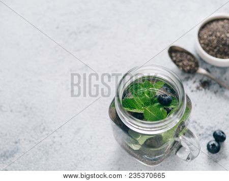 View From Above Chia Water In Mason Jar With Mint And Blueberry On Gray Cement Background. Chia Infu