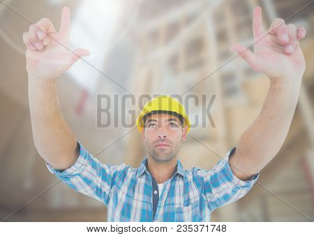 Construction Worker with hands up in air in front of construction site