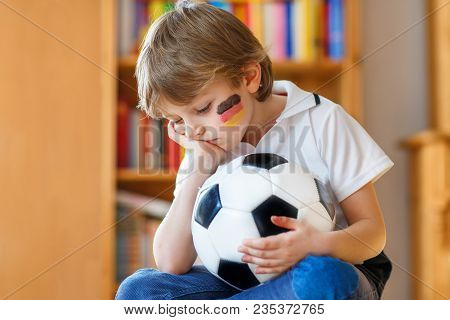 Little Blond Preschool Kid Boy With Ball Watching Soccer Football Cup Game On Tv. Sad, Crying And De