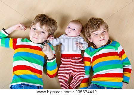 Two Happy Little Preschool Kids Boys With Newborn Baby Girl, Cute Sister. Siblings, Twins Children A