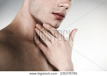 Serious Undressed Male Holding Chin By Hand. He Having Freckles On Nose. Earnest Concept. Close Up