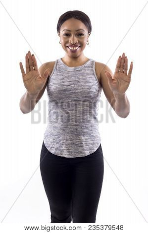 Black Female Wearing Athletic Outfit On A White Background As A Fitness Trainer Doing A Stop Gesture