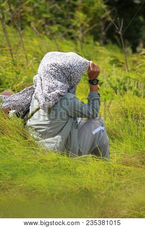 A Woman Sitting In A Windy Meadow.