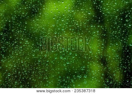 Water Drops On Glass Green Window. Rain Drops Of Water On Summer Window, Green Garden Or Forest Back