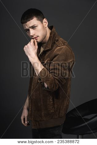 Portrait Of Tough Assertive Guy Keeping Cigarette. He Isolated On Black Background. Confidence Conce