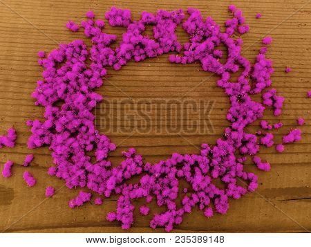 Round Pink Flowers Frame. Round Frame Of Purple Pink Little Flowers On Wooden Background. Text Plase