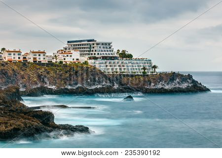 Rocky Coast Of Tenerife With Modern Hotel, Long Time Exposure