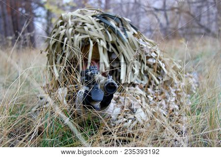Military Man Armed Sniper Rifle Gun In Combat Position. Armed Man In Soldier Camouflage With Sniper