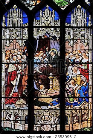 PARIS, FRANCE - JANUARY 04, 2018: The death of Louis XIII in the presence of St Vincent de Paul, Anne of Austria, the future Louis XIV and Cardinal Mazarin, stained glass in St Severin church in Paris