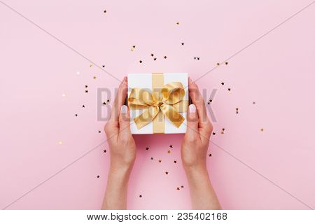 Womans Hands Holding Gift Or Present Box Decorated Confetti On Pink Pastel Table Top View. Flat Lay