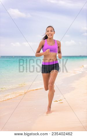 Running jogging woman on beach at Caribbean travel vacation living a healthy lifestyle in sportswear sports bra and run shorts with fit legs. Happy young Asian girl.